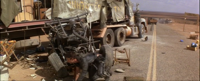 Max hunts out food and fuel from a wrecked truck, while the 'interceptor' is visible in the background.