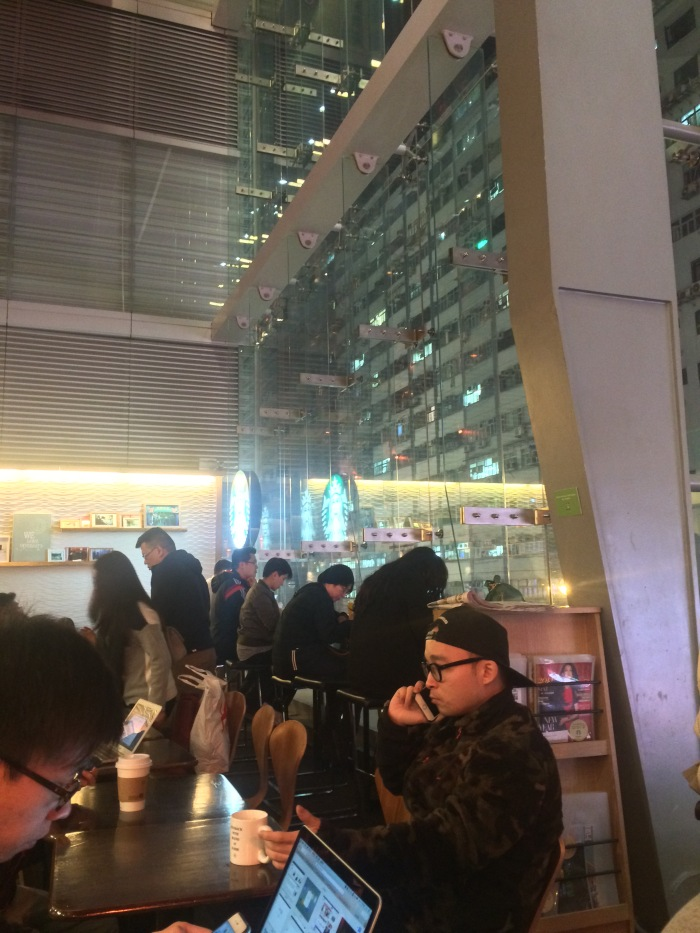 The modernist glass face of Starbucks on Nathan road made Kowloon look like a 'behind the glass' museum display