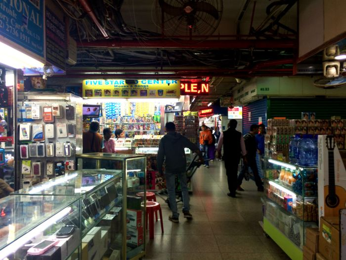 Inside the Chungking Mansions Mall. Note the exposed piping and fans. This area gets very hot in Summer, but doesn't have any actual cooling.